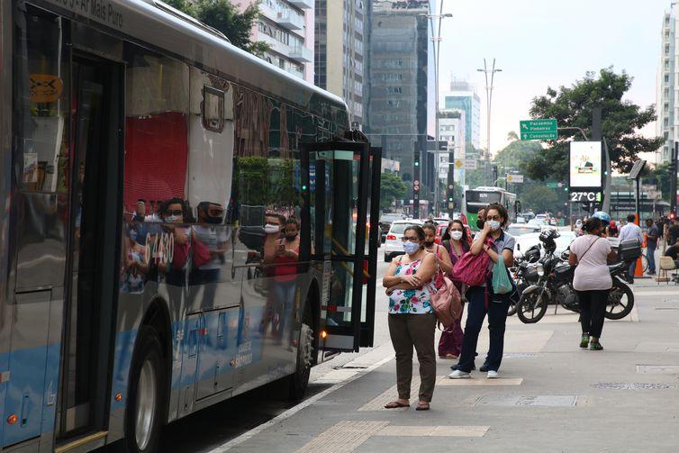 Usuários do transporte público esperam ônibus em ponto da Avenida Paulista, durante a fase vermelha da pandemia de covid-19 na capital.